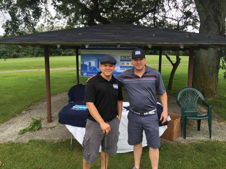 Chicago Fire Protection President John LaGiglia and Vice President Joseph Regan pose at a golf outing they have sponsored and stand in front of a table advertising their business.